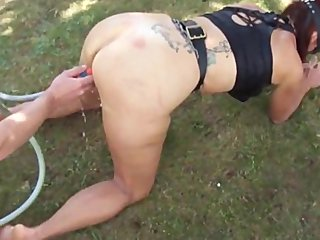 husband gives wife enema in the backyard
