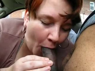 fat mature gives blowjob to young dark on car